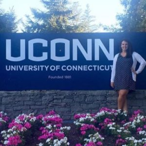 Morgan Sutton next to UConn campus sign