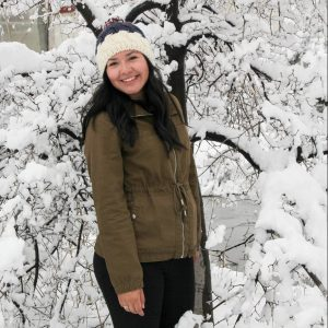 April Cano in front of snow covered tree